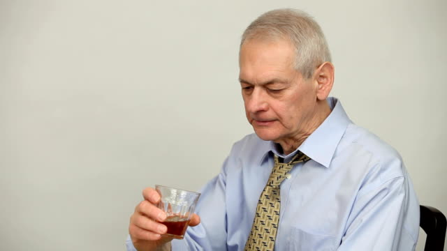 Man in shirt and tie in depressed state getting drunk