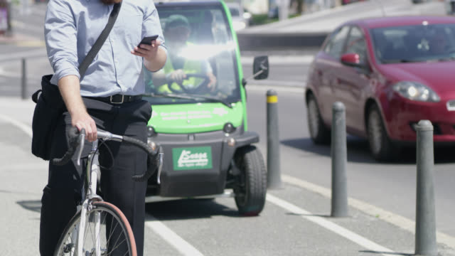 vídeos de stock, filmes e b-roll de é homem de camisa usando um telefone inteligente na calçada de uma rua movimentada - carro elétrico