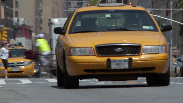 A man in shorts hails a cab in New York city on 7th Avenue.  The cab stops and picks him up and they drive off.