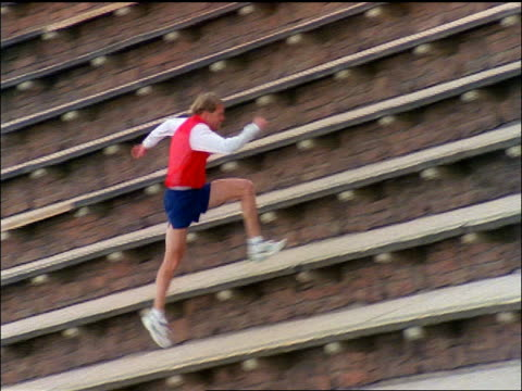 pan man in shorts running up stadium steps / red rocks amphitheater - running shorts stock videos & royalty-free footage