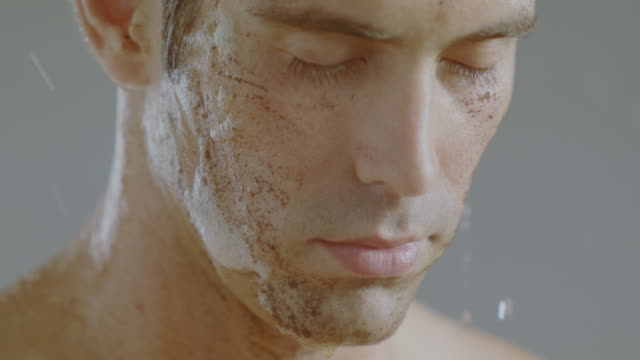 Man in shower washing off remains of facial mud mask.