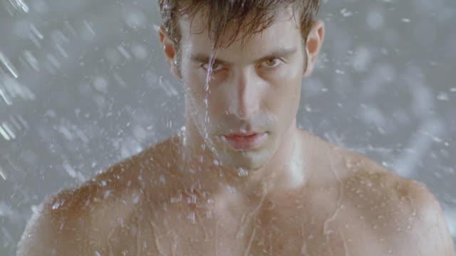 vídeos de stock e filmes b-roll de man in shower washing off remains of facial mud mask. - homem tomando banho