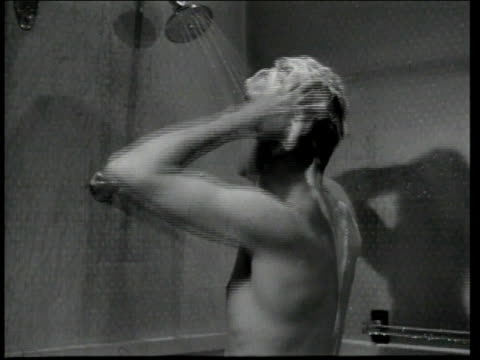 1947 MONTAGE Man in shower wearing boots washing his hair and rinsing it / United States