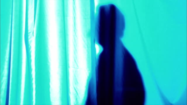 a man in silhouette strolls past a blue, neon curtain. - behind stock videos & royalty-free footage