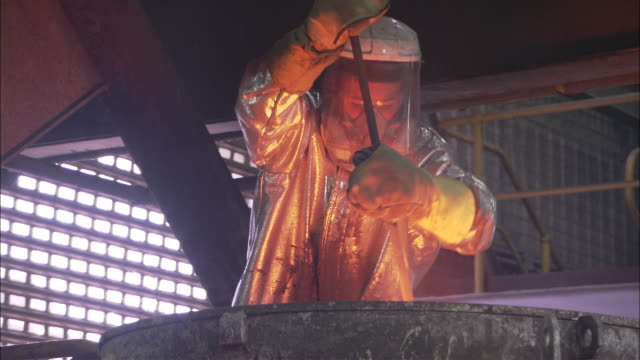 ms man in silver suit with protective plastic mask stirs and prepares gold, kalgoorlie, western australia, australia - fire protection suit stock videos & royalty-free footage