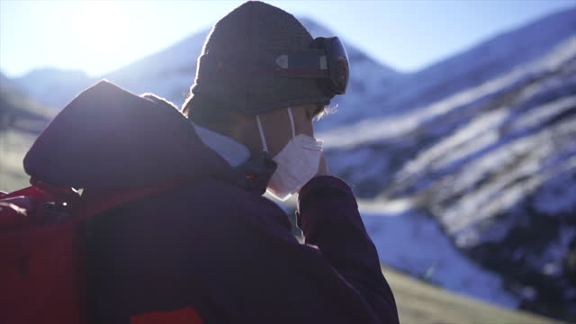 man in ski suit putting on a health mask in the mountains in switzerland - woolly hat stock videos & royalty-free footage