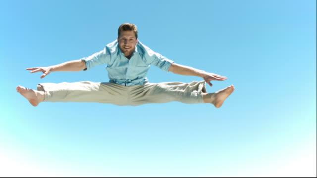 man in slow motion making a straddle jump - nur junge männer stock-videos und b-roll-filmmaterial