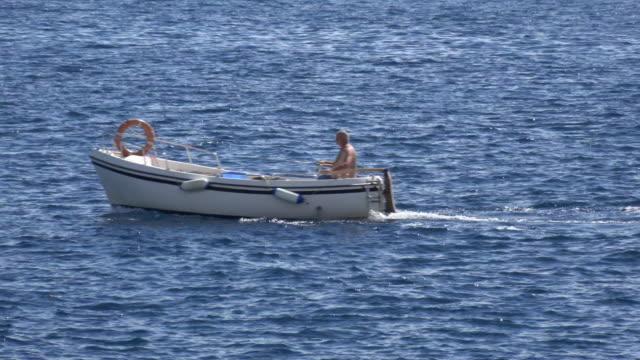 man in small boat on mediterranean sea - island of elba stock videos & royalty-free footage