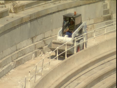 man in small digger drives around the marble panathinaikon stadium during construction for the 2004 olympics athens - panathinaiko stadium stock videos & royalty-free footage