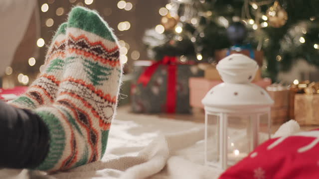 a man in socks with a christmas pattern sits on a blanket near the christmas tree and moves his legs - sock stock videos & royalty-free footage