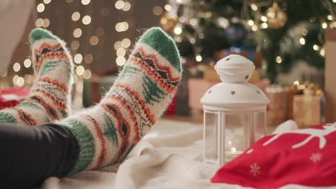 stockvideo's en b-roll-footage met een mens in sokken met een kerstmispatroon zit op een deken dichtbij de kerstboom en krast één been met andere - comfortabel