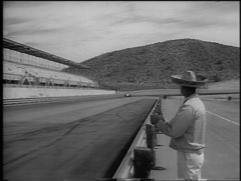 b/w 1965 man in sombrero watching race car testing on phoenix international raceway / newsreel - 試運転点の映像素材/bロール