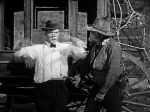 b/w 1924 man in stagecoach holdup pulling off bandana of robber / feature - slapstick stock videos & royalty-free footage