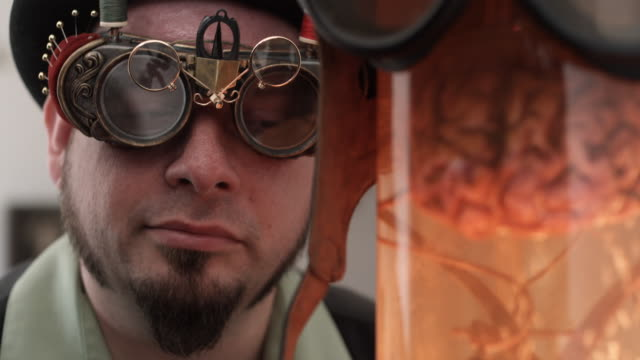 cu man in steampunk outfit with bizarre sewing goggles looking at brain in jar, middletown, connecticut, usa - ziegenbart stock-videos und b-roll-filmmaterial