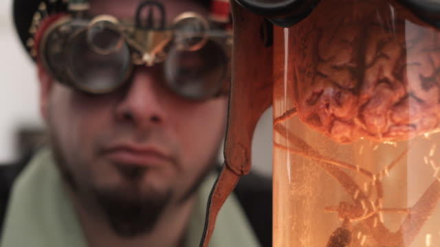 CU R/F Man in Steampunk outfit with bizarre sewing goggles looking at brain in jar, Middletown, Connecticut, USA