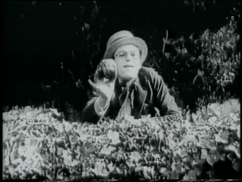 b/w 1918 man in straw hat behind hedge throwing object offscreen / short - straw hat stock videos & royalty-free footage