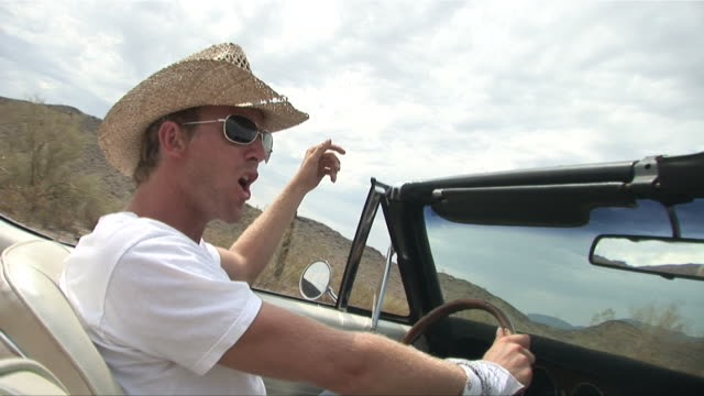 ms passenger pov man in straw hat driving convertible through the desert and shouting/ man's hat blowing off as he inches up in his seat/ scottsdale, arizona - see other clips from this shoot 1050 stock videos and b-roll footage
