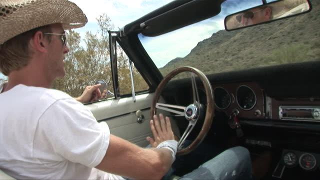 ms passenger pov man in straw hat driving convertible through the desert/ zi cu man's hands on steering wheel/ scottsdale, arizona - セージブラッシュ点の映像素材/bロール