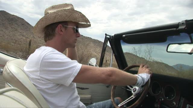 ms passenger pov man in straw hat driving convertible through the desert/ scottsdale, arizona - straw hat stock videos & royalty-free footage