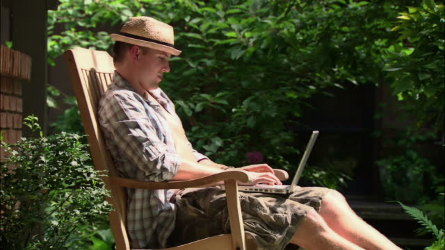ms man in straw hat using laptop in rocking chair/ man closing laptop/ texas - rocking chair stock videos & royalty-free footage