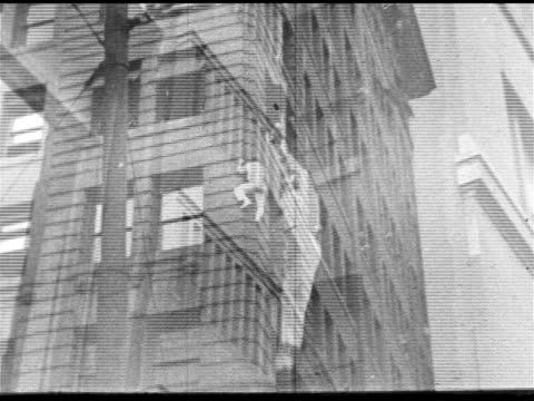 vidéos et rushes de man in street clothes climbing up side of city building td ms male standing on hands on rooftop falling over onto roof - 1910 1919