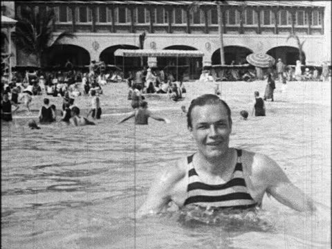 vidéos et rushes de b/w 1924 man in striped swimsuit in surf talking to camera / hotel in background / miami beach / industrial - 1924