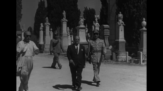 vídeos de stock e filmes b-roll de man in suit and a military or police official walk from graveyard with elaborate grave markers - bandido