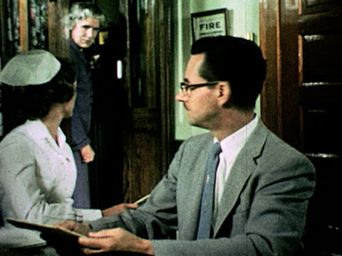 / man in suit and nurse sit at table, man talks to nurse and holds notepad ; nurse relays info to woman watching in background on january 01, 1955 - 1955 stock videos & royalty-free footage