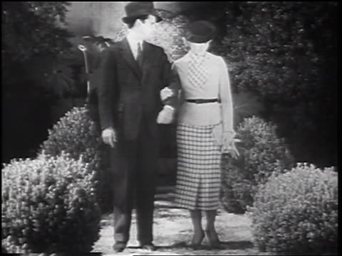b/w 1935 man in suit + blonde woman walking together past bushes offscreen - 1935 stock videos & royalty-free footage
