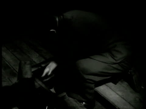 vidéos et rushes de dramatization night man in suit crouched down placing rifles beneath floorboards male hands putting ammunition on top of rifles under floor replacing... - world war 1