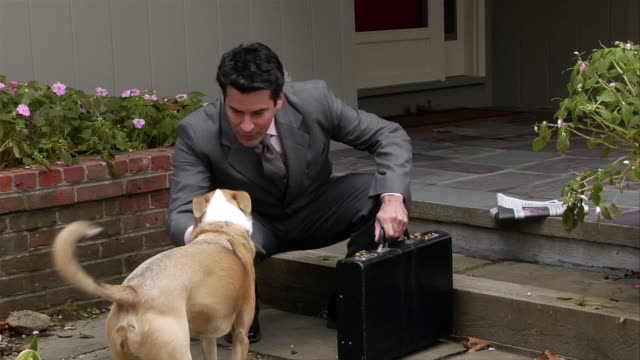 Man in suit crouching down to pet dog outside house before leaving for work / waving to carpool offscreen