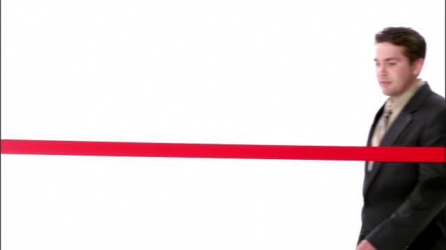 vídeos de stock, filmes e b-roll de ms, man in suit cutting red ribbon, studio shot - cortando fita