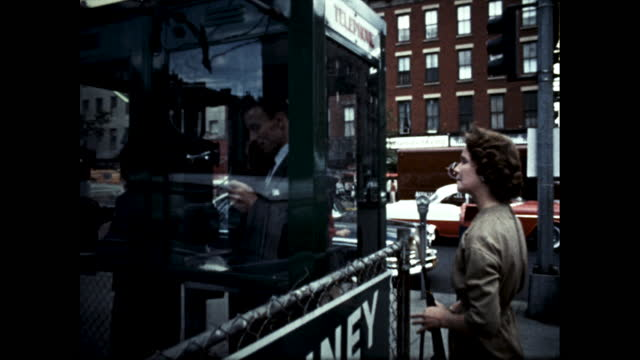 vídeos y material grabado en eventos de stock de man in suit flipping through a phone book; woman waiting for man to finish using the phone booth; man makes a call while woman waits impatiently - directorio