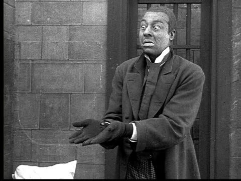 stockvideo's en b-roll-footage met 1916 b&w ms man (bert williams) in suit in prison cell playing imaginary poker game  - racisme