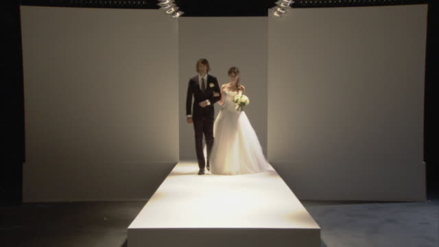 WS Man in suit kissing hand of woman modeling wedding dress on catwalk / London, England, UK