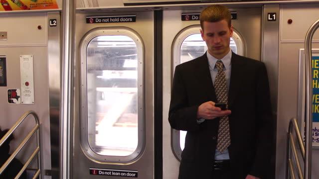 man in suit on subway using his phone - 乗り物内部点の映像素材/bロール