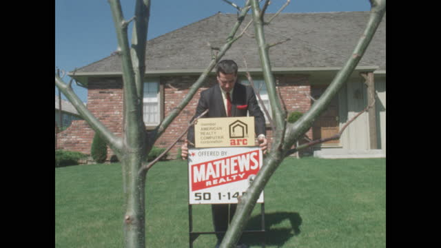 1968 man in suit plants for sale sign in lawn of suburban home viewed through branches - salesman stock videos & royalty-free footage