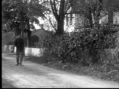 1916 b&w ws man in suit running on dirt road/ two men catching up with him and talking to him  - 1916 stock videos & royalty-free footage