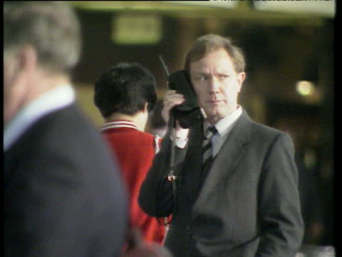 Man in suit standing still while using large mobile phone people pass around him UK; 1980s