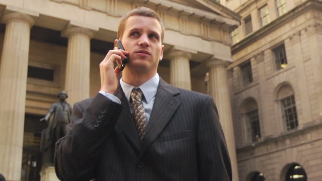 vidéos et rushes de man in suit talking on phone in front of city monument - column