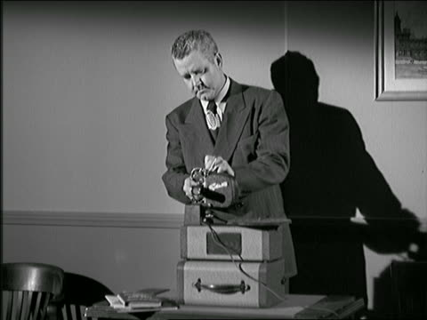 b/w 1948/49 man in suit threading projector with film for presentation - einzelner mann über 40 stock-videos und b-roll-filmmaterial