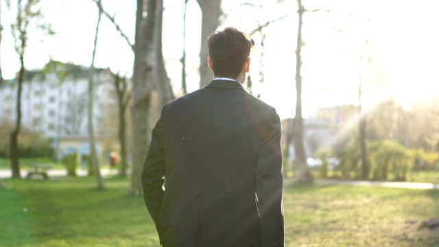 man in suit walking in park - white collar worker stock videos & royalty-free footage