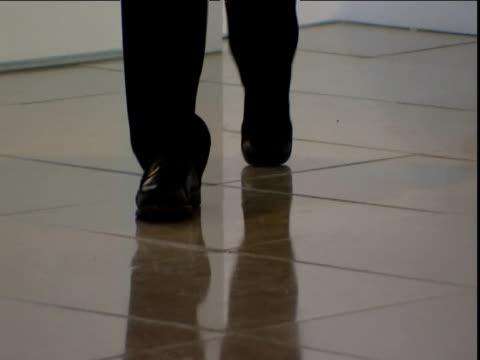 man in suit walks across tiled floor towards camera - 反射点の映像素材/bロール