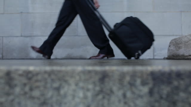 CU of man in suit with suitcase walking