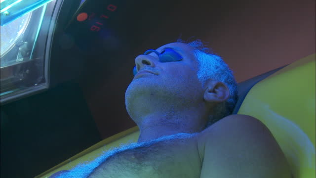 stockvideo's en b-roll-footage met cu man in sunbed / bruxelles city, bruxelles, belgium - gebruind
