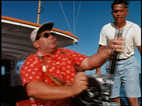1960 man in sunglasses + cap reeling in fishing rod on back of boat as second man watches / Hawaii