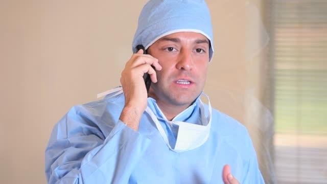 vídeos de stock e filmes b-roll de ms tu man in surgical scrubs talking on smartphone in hospital / richmond, virginia, usa - bata cirúrgica