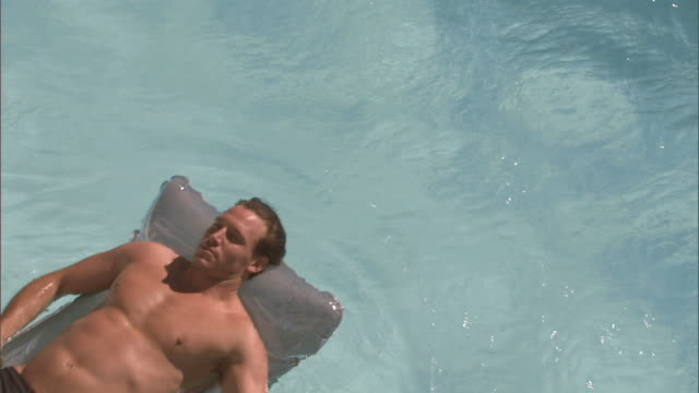 vidéos et rushes de oh ms man in swim trunks floating past on inflatable pool raft/ cape town, south africa - bain de soleil