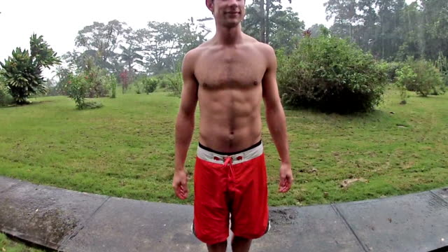 vídeos de stock e filmes b-roll de man in swimsuit pretending to take shower in heavy tropical rainfall. - só um homem de idade mediana