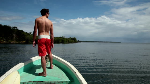 vidéos et rushes de man in swimsuit riding in bow of boat on tropical ocean and beach in background. - seulement des jeunes hommes